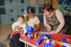 Health visitor talking to family worker with child sitting on her knee,