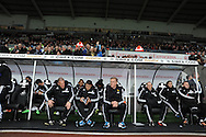 Swansea city's manager Garry Monk (c) with his coaching staff sits in dugout ahead of k/o. Barclays Premier league, Swansea city v Crystal Palace match at the Liberty Stadium in Swansea, South Wales on Sunday 2nd March 2014.<br /> pic by Andrew Orchard, Andrew Orchard sports photography.