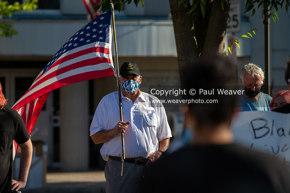 A man wearing a US Army veteran hat holds an American flag at a Black Lives Matter protest in Lock Haven, PA.