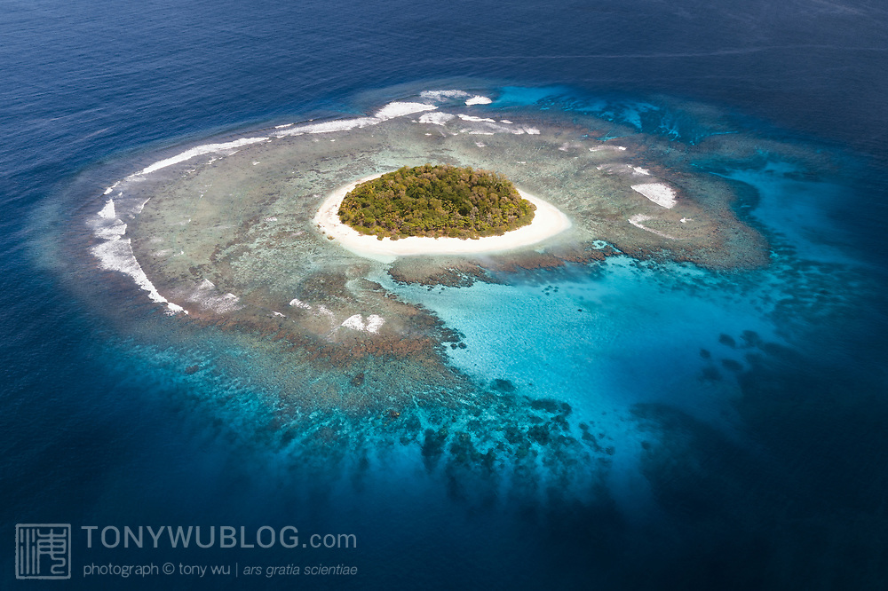 Aerial view of Luahaipo island in the Vava'u island group of the Kingdom of Tonga, showing fringing coral reef structure and white sand beach surrounding the island