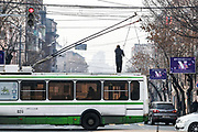 A man works on top of a trolleybus nearby city centre in Yerevan, Armenian capital on Thursday, Jan 14, 2021. The most common type of public transportation is the minibuses, especially when it comes to routes outside Yerevan. There are buses and even trolleybuses too. All the signs and names of the bus stops and areas on city buses and marshrutkas are in Armenian. If there are no free seats on the bus, doesn't mean you cannot get on the bus at all. (Photo/ Vudi Xhymshiti)