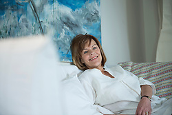 Senior woman sitting on couch in living room, smiling
