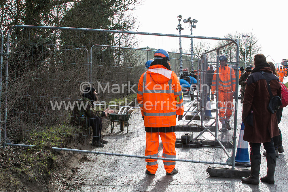Harefield, UK. 8 February, 2020. An environmental activist sits behind Heras-style fencing erected by HS2 engineers on Harvil Road in the Colne Valley in preparation for tree felling work for the high-speed rail link. Environmental activists based at a series of wildlife protection camps in the area used a variety of tactics to prevent the tree felling work, for which road and rail closures had been implemented, for the duration of the weekend for which it had been scheduled.