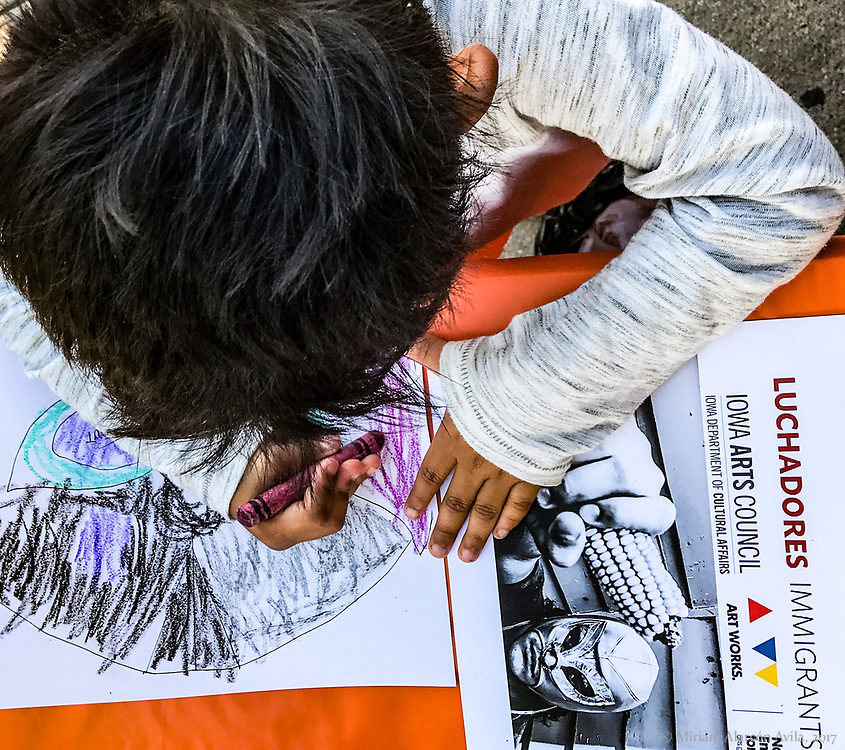 A Latino boy is using crayons to color a paper luchador mask during the Latino festival in Iowa City in 2017.