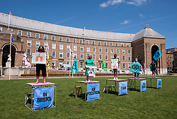 "© Licensed to London News Pictures;23/06/2020; Bristol, UK. Extinction Rebellion's Five a Week campaign for clean air stages a symbolic, theatrical action highlighting the number of premature deaths in Bristol due to air pollution. They have set up 5 cubes on College Green in front of City Hall with the message ""In Bristol, air pollution causes 5 deaths each week"". People are invited to take part and bring their own placard and message around air pollution and step on top of a cube for 2 minutes in silence, then allow the next person to take their place until the ""death count"" comes to 296. Participants are then invited to place their placards on the Green to create a sticking sea of messages. Social distancing measures are in place and everyone is required to participate wearing a mask. Extinction Rebellion demand urgent action from Bristol City Council & WECA (West of England Combined Authority) to protect people's lungs and protect the planet, saying health is intrinsically linked to the health of the environment. XR want Clean Air Equality for Life, not just for the coronavirus Covid-19 lockdown, saying we have a unique opportunity as we come out of lockdown to envision a Bristol that puts people's health and the health of the planet first, and put pressure on elected officials to help build the city back better. Photo credit: Simon Chapman/LNP."
