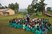 At Nyamiyaga primary school the Bwindi Community Hospital run health outreach programs. Reverend Sam, Head of Community Health, works on a nutrition game with the children. As part of the outreach programme they cover 32 primary schools and 5 secondary schools in the region as well as many communities. The main Bwindi Community Hospital is in Buhoma village on the edge of the Bwindi Impenetrable Forest in Western Uganda. It serves around 60,000 people from the surrounding area.
