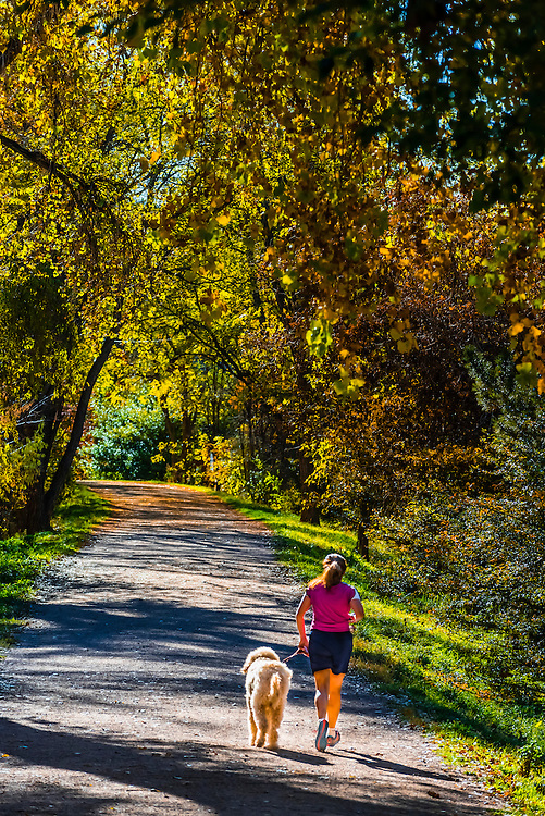Woman running with her dog on the Highline Canal path on an Autumn afternoon, Littleton, Colorado USA.