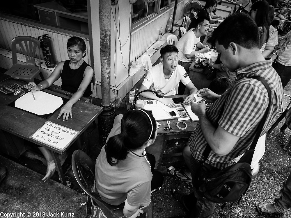 22 DECEMBER 2018 - CHANTABURI, THAILAND: A Chinese gem buyer talks to a man selling gems in the gem market in Chantaburi. The gem market in Chantaburi, a provincial town in eastern Thailand, is open on weekends. Chantaburi used to be an active gem mining area in Thailand, but the mines are played out now. Now buyers and sellers come from around the world to Chantaburi for the weekend market. Many of the stones come from Myanmar, others come from mines in Afghanistan and Africa.       PHOTO BY JACK KURTZ