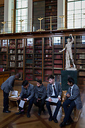Schoolboys visiting the Enlightenment Gallery of the British Museum sit on a bench in front of Rondanini Faun, a 2nd century Roman statue, on 28th February 2017, in London, England.