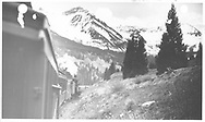 Leased D&RGW #319 going downgrade northbound from Lizard Head with photo taken from RMRRC excursion train.  Pyramid Peak is in the background.<br /> RGS  Lizard Head, CO  Taken by Kindig, Richard H. - 5/31/1947