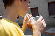 very thirsty young boy drinking from two cups with two straws