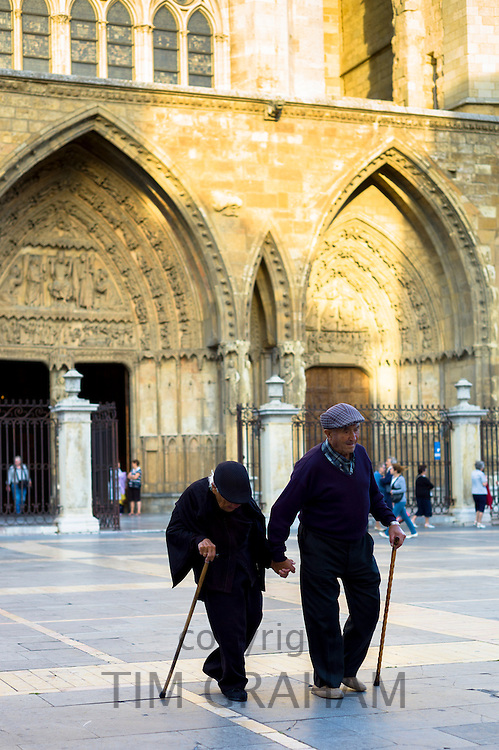 Elderly couple with walking sticks leave after Catholic Mass at Santa María de León Cathedral in Leon, Castilla y Leon, Spain