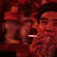 Asia, Vietnam, Buddhist monk smoking cigarette at small temple along Yen Stream near Perfume Pagoda (Chua Huong)