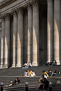 Visitors rest on the steps of St. Paul's Cathedral in the forecourt of this famous London landmark, on 16th September 2020, in London, England.