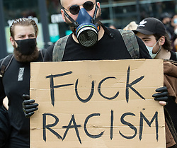 "© Licensed to London News Pictures. 06/06/2020. Manchester, UK. A man wearing a gas mask and carrying a "" Fuck Racism "" placard . Tens of thousands attend a Black Lives Matter demonstration against police violence , centred in Piccadilly Gardens in Manchester City Centre . Protests have and are being held around the world , after George Floyd was killed whilst being restrained by police in Minneapolis on 25th May 2020 . Photo credit: Joel Goodman/LNP"