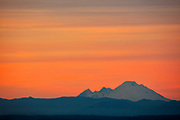 Several bands of clouds streak across the sky over Mount Baker in Washington state at sunset. Mount Baker, at 10,781 feet (3,286 meters), is the third largest volcano in Washington state and last erupted in 1880.