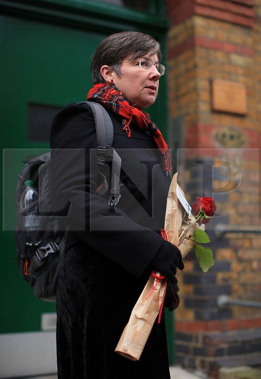 """© Licensed to London News Pictures . 11/03/2014. Sara Friday, a former train driver and  member of the RMT brings flowers to the RMT head office, London, to paid tribute to Bob Crow, General secretary of the Rail Maritime and Transport union, who has died today (11/03/14) at the age of 52 of a heart attack. Her note reads: """"You were a great leader, great public coacher. You could  really speak to the working class. You will be missed. Sara Friday."""" London, UK.   Photo credit: Isabel Infantes /LNP"""