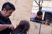 Xóchitl de la Paz corta cabello en la calle Galicia donde se ubicaba su negocio, destruido tras el sismo del 19 de septiembre. Su madre, Salomé, falleció tras el colapso del edificio, en esquina con Niños Héroes. Mientras espera ser atendida por autoridades, Xóchitl gana 35 pesos (2 USD aprox) por corte de cabello. 24 de octubre de 2017. // Xóchitl de la Paz makes a haircut in the corner of Galicia and Niños Héroes, in the street where her shop was installed. Her mother, Salomé, died during the earthquake. In her makeshift place, with a mirror hanging on a triplay sheet, Xóchitl earns 35 Mexican pesos (2 USD aprox) for each haircut. October 24th, 2017. (Prometeo Lucero)