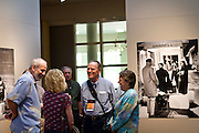 Family and friends gather around the impressive prints of the 1966 Yearbook exhibit in Faulconer Gallery.