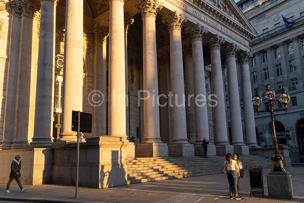 With most Londoners still working from home, friends talk beneath the columns of Royal Exchange while walking along a quiet Threadneedle Street during the evening rush-hour during the third lockdown of the Coronavirus in the City of London, the capitals financial district, on 26th February 2021, in London, England. At the top of Doric and Ionic columns with their ornate stonework, powerfully strong lintels cross, bearing the load of fine artistry and carvings which feature the design by Sir William Tite in 1842-1844 and opened in 1844 by Queen Victoria whose name is written in Latin Victoriae R. It's the third building of the kind erected on the same site. The first Exchange erected in 1564-70 by sir Thomas Gresham but was destroyed in the great fire of 1666. It's successor, by Jarman, was also burned down in 1838. The present building is grade 1 listed and cost about £150,000.