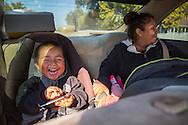 """Easton, CA<br /> Soledad Magana (23 years old)<br /> Hugo Magana (27 years old) <br /> Cesar Magana (2.5 years)<br /> Camila Magana (1 year old)<br /> This shot: Soledad and her children laugh happily as they head home with fresh food.<br /> <br /> Soledad and her mother stood hand in hand at the mobile pantry for the first time. <br /> <br /> Soledad's husband, Hugo, arrived in a small white car with their two children, Cesar and Camila, in the backseat.  As Soledad collected the distribution, Hugo worked to pack up the trunk.  The car made its way back to their home in Easton with the family of four and a load of fresh bananas, carrots, bread, juices, lettuce, persimmons, and more. <br /> <br />  The family's home was a small trailer.  As Hugo unloaded the distribution, Soledad held her baby girl in her arms and kept a careful ear out for little Cesar, busy making toys out of everything he could find.  Soledad smiled at the sight of the full kitchen.  """"Thank God,"""" she sighed, knowing that there would be food on the table that night. <br /> <br /> The young family had recently faced a series of hardships.  Due to the drought, Hugo was out of work.  The majority of his family and friends returned to Mexico, leaving them without a circle of support. So they moved to Easton to be closer to Soledad's family.  Soledad also struggles to find work.  Without a GED and no English her options are limited.  However, she dreams of going back to school to be a dental hygienist.  To make ends meet in the short term, Hugo was hoping to find a job picking oranges or pruning that week.<br /> <br /> Family and extra support are what help this young couple survive.  $230 worth of food stamps monthly and the distribution from the community food bank both help them to make their rent payment of $370.  Once Cesar starts school, Soledad is grateful he'll be able to eat at the elementary cafeteria.  As food insecurity falls off their list of things to alleviate—for now—Hugo and Soledad ca"""