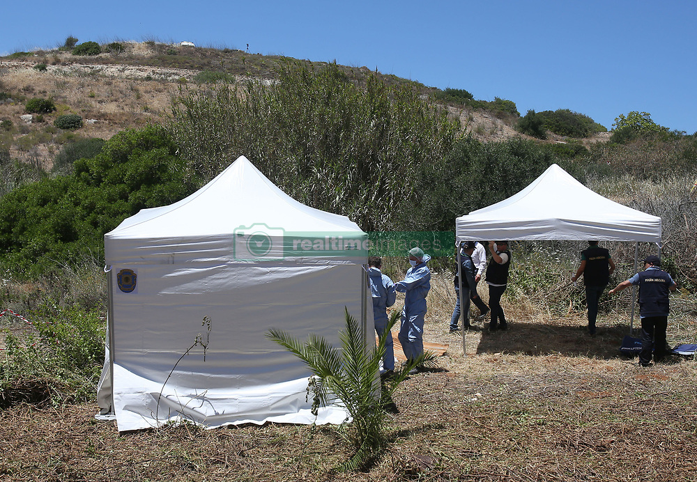 File photo dated 04/06/14 of forensic police officers investigating the disappearance of Madeleine McCann examining an area of wasteland outside the town of Praia da Luz in Portugal.