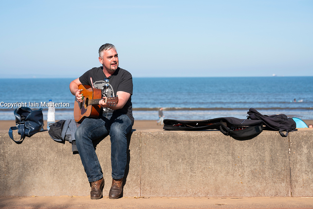 Portobello, Scotland, UK. 3 April 2021. Easter weekend crowds descend on Portobello beach and promenade to make the most of newly relaxed  Covid-19 lockdown travel restrictions and warm sunshine with uninterrupted blue skies. Pic;  A busker has returned. Iain Masterton/Alamy Live News