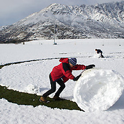 Simon Healy, 11 (front) and his brother Nicholas, 7, from Auckland,  use all their effort to make large snowballs at the Events Centre Fields, Queenstown, with the Remarkables mountain range in the background after fresh winter snow falls. Queenstown, Central Otago, South Island, New Zealand. 10th July 2011. Photo Tim Clayton..