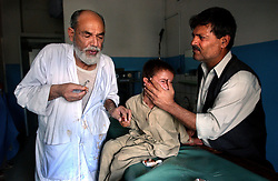 KABUL,AFGHANISTAN - AUGUST 29: Dr. Abdul Qader Ghafari stitches the hand of  Rashid, 6, in the Indira Ghandi Hospital for Children August 29, 2002 in Kabul, Afghanistan. The hospital has 300 beds but usually it is filled at double capacity with only 118 doctors. (Photo by Ami Vitale/Getty Images)