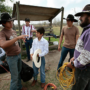 Nathan Losoya, left, 16, talks to his rodeo coach Frank Quesada, right, as Cosme Escamilla, center, 12, listens following a practice at Quesada's Weslaco ranch. The students spent the morning practicing on their barrel and the bull before traveling to Edinburg to compete in an open rodeo. <br /> Nathan Lambrecht/The Monitor