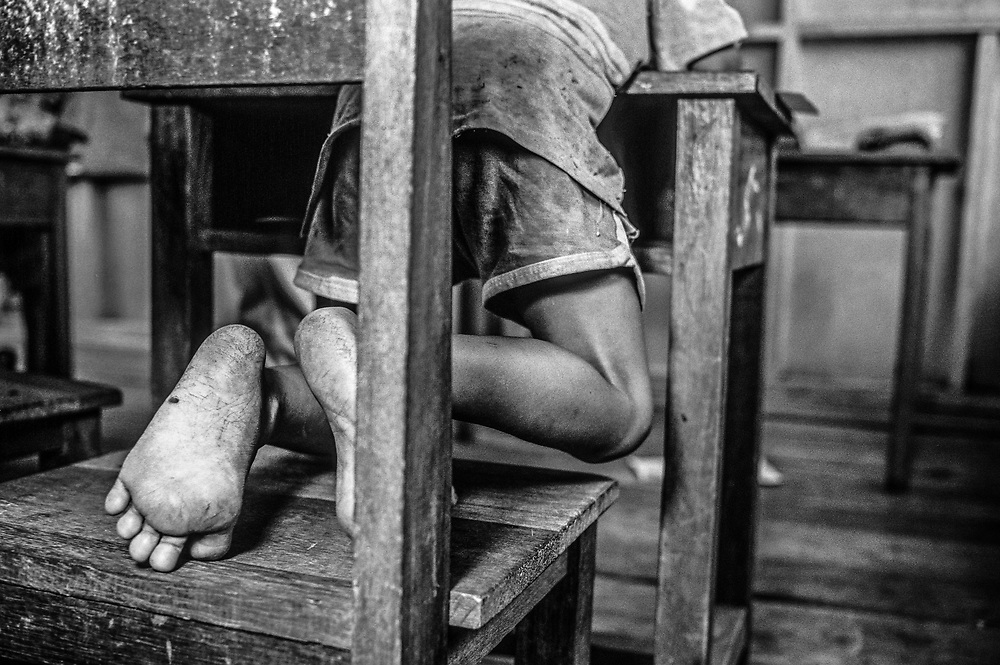 Close up of Childs bare feet in a school classroom, Malaysia, Sabah, Borneo 1992