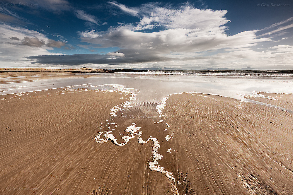 Waves creep over a sand bar at Silver Bay cove on North West Anglesey whilst clouds scurry overhead
