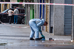 © Licensed to London News Pictures. 23/09/2019. London, UK. A forensic investigator looks over clothing and a blood covered shoe where a man in his 20's was found injured outside a shop in The Broadway, Southall. The man was taken to hospital suffering from a stab injury; he we was pronounced dead at 05:26 BST. Photo credit: Peter Manning/LNP