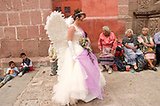 07 APRIL 2004 - SAN MIGUEL DE ALLENDE, GUANAJUATO, MEXICO: A woman portraying an Angel walks into the Church of the Oratorio before a Holy Wednesday Stations of the Cross procession through San Miguel de Allende, GTO, MEX. Semana Santa, the week before Easter is celebrated with extreme piety in central Mexico. San Miguel, which was founded in the 1600s, is one of Mexico's premier colonial cities. It has very strict zoning and building codes meant to preserve the historic nature of the city center. About 7,500 US citizens, mostly retirees, live in San Miguel. PHOTO BY JACK KURTZ