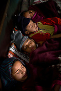 A rural Punjabi Sikh family sleeping together in a large bed before going to school, Chita Kalaan village, Punjab, India