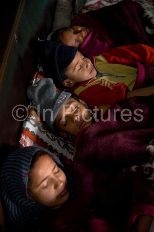 A rural Punjabi Sikh family sleeping together in a large bed before going to school, Chita Kalaan village, Punjab, India