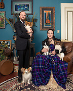 Husband and wife all dressed up for portrait at their home with their five dogs