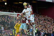 Andy Carroll of West Ham United defending the ball over Ashley Williams, the Swansea City Captain (c). Barclays Premier league match, West Ham Utd v Swansea city at the Boleyn ground, Upton Park in London on Sunday 7th December 2014.<br /> pic by John Patrick Fletcher, Andrew Orchard sports photography.