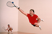 A racketball player dives for a ball.