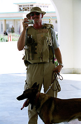 A US Department of Defence's contractor, with his anti-explosive shepperd dog, takes a picture of a journalist at the Kandahar Governour's house.