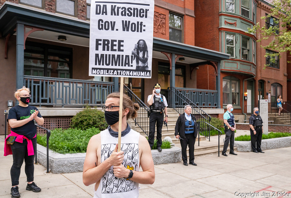 Standing in front of Philadelphia police, a protester holds a sign calling for the release of Mumia Abu-Jamal a journalist and political activist who was convicted of murder and sentenced to death in 1982 for the 1981 murder of Philadelphia police officer Daniel Faulkner.