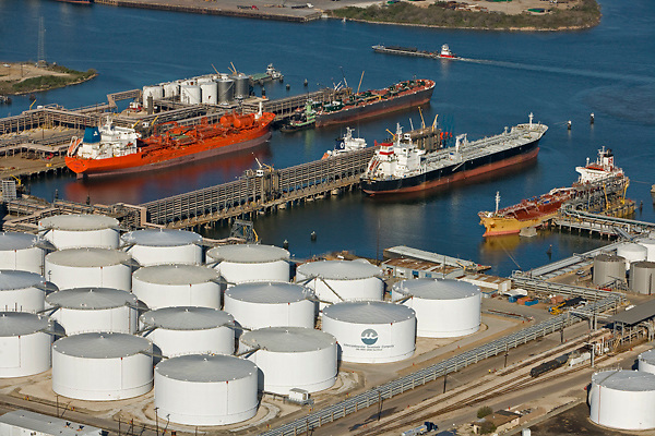 Aerial view of tankers docked in the Port of Houston beside a tank farm