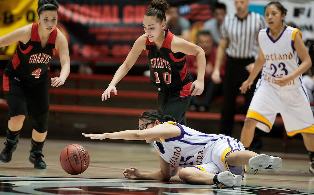 Kirtland Central's Ametia Begay streches out for a loose ball as Sydney Mares of Grants moves in from behind. Kirtland Central defeated Grants 53-49 in the AAAA semifinals Thursday afternoon in Albuquerque at The Pit.