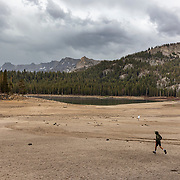 A late afternoon thunderstorm drops much needed precipitation on Horseshoe Lake that has shrunk to precarious levels in July, 2021 due to a prolonged drought. A young man runs through the rain toward the lake.