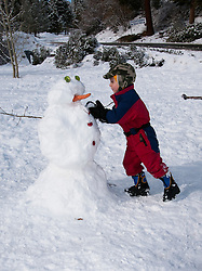 California, Lake Tahoe: Child makes a snow man at  North Lake Tahoe Regional Park.  Photo copyright Lee Foster.  Photo # cataho107580