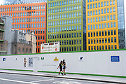 People wearing face masks walk past the construction site behind the colourful Google offices building on 13th August 2020 in London, United Kingdom. Google is an American multinational technology company specializing in Internet-related services and products.