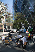 At the base of the Gherkin, office and city workers enjoy the sunshine in the newly refurbished square, surrounded by new high rise modern architecture in the City of London, England, United Kingdom. As Londons financial district grows in height, the classical buildings are being dwarfed by the towers and skyscrapers of glass.
