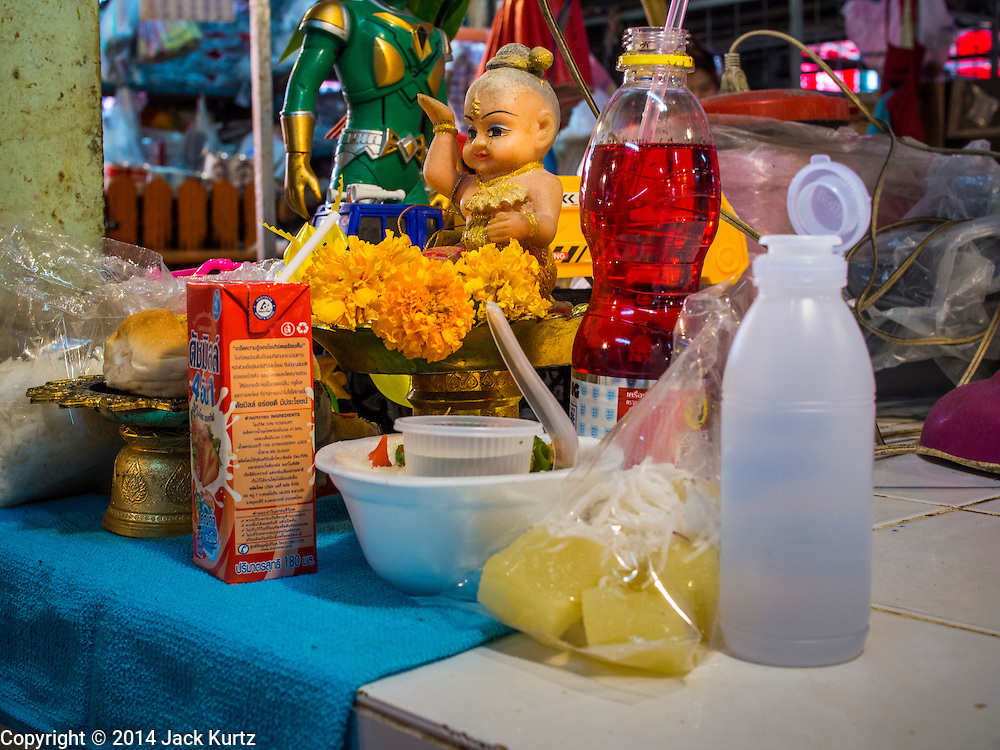 19 NOVEMBER 2014 - BANGKOK, THAILAND: A shrine in a shop in Khlong Toei Market in Bangkok. Between July and September the economy expanded 0.6 percent compared to the previous year, the National Economic and Social Development Board (NESDB) reported. Thailand's economy achieved a weak 0.2 per cent growth across the first nine months of the year. The NESDB said the Thai economy is expected to grow by 1 percent in 2014. Authorities say the sluggish growth is because tourists have not returned to Thailand in the wake of the coup in May, 2014, and that reduced demand for computer components, specifically hard drives, was also hurting the economy. Thailand is the leading manufacturer of computer hard drives in the world. The Thai government has announced a stimulus package worth $11 billion (US) to provide cash handouts to farmers and promised to speed up budget spending to boost consumption.   PHOTO BY JACK KURTZ