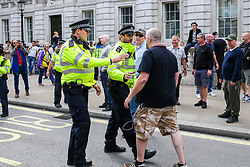 "© Licensed to London News Pictures. 07/09/2019. London, UK. A police officers confront a Pro Brexit protester in Whitehall as anti-Brexit protesters take part in ""Defend our Democracy and Stop Brexit"" demonstration in Whitehall, Westminster. The protesters are demonstrating against the British Prime Minister Boris Johnson's intention to prorogue Parliament until 14 October. Photo credit: Dinendra Haria/LNP"
