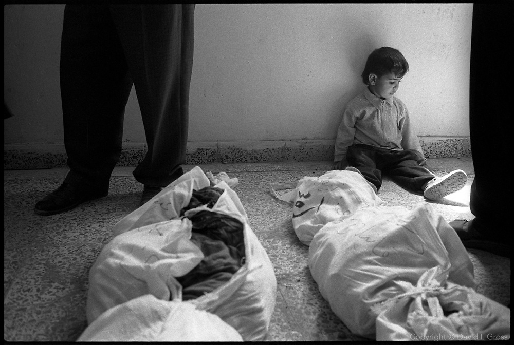 A boy waits for his mother who is searching for her missing relatives among the bones in shrouds that fill the gymnasium of the local sports center in Al-Musayab, Iraq. The center is now the home of an Iraqi human rights organization which is overseeing the exhumations of bodies from local mass graves. People come from all over to check the clothing and ID cards of the bodies, looking for relatives.